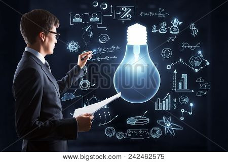 Attractive Young European Businessman With Creative Business Sketch On Wall. Education, Technology,