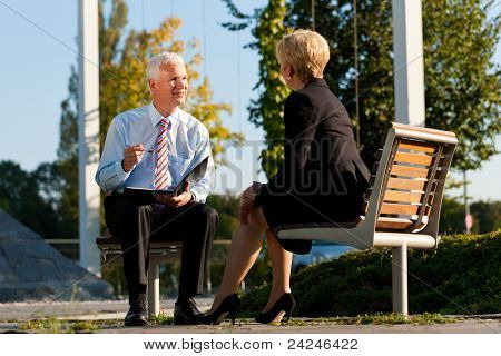 Business coaching outdoors - a man and a woman have a coaching discussion poster