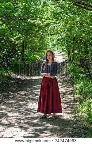 A Girl In A Red Skirt Is On A Forest Road