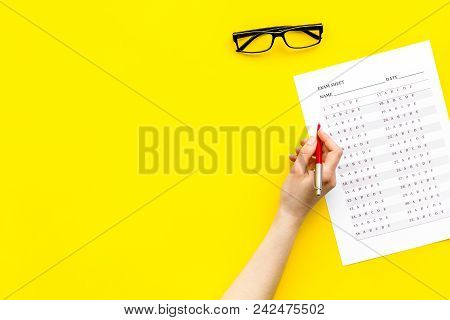 Take The Exam, Write The Exam. Hand With Pen Near Exam Paper On Yellow Background Top View.