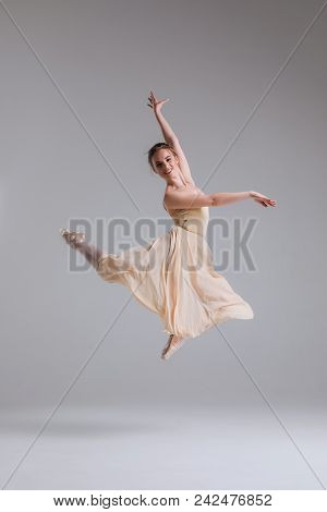 Enjoy Moving Your Body With Ease! Young Cheerful Attractive Ballerina In Jump Showing Split Isolated