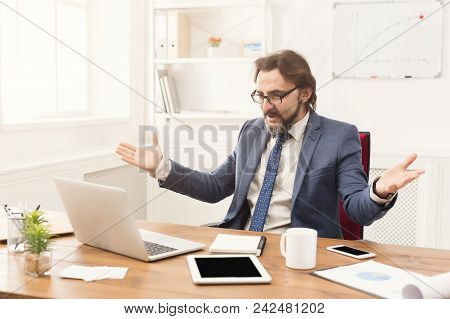 Surprised Businessman Looking At Laptop At His Office Working Place. Portrait Of Middle-aged Employe