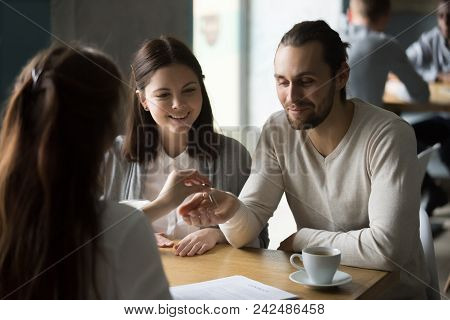 Happy Millennial Couple Getting Keys To New House From Realtor In Cafe, Young Customers, Renters Or