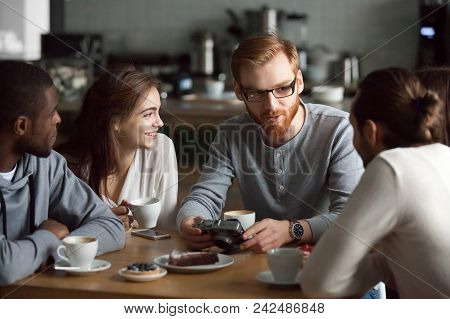 Young Redhead Guy Holding Camera Showing Photos Sharing Recent Memories Or Travel Impression Hanging