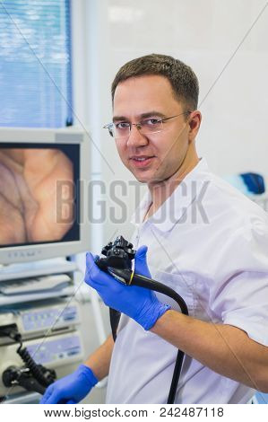 Proctologist Holding An Anoscope Against A Proctological Chair. In The Hospital.