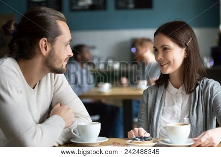 Happy Millennial Couple In Love Talking Sitting At Coffee House Table Together, Smiling Young Attrac