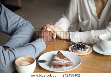 Interracial Couple Holding Hands Sit At Cafe Table, African Black Man And White Woman In Love Enjoy