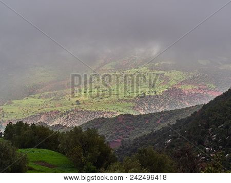 Fog Descends To The High Valley Of The High Atlas, Through The Clouds There Are Green Fields On The