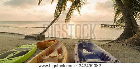 Kayaks Sitting On The Beach At Dawn With A Beautiful Sunrise