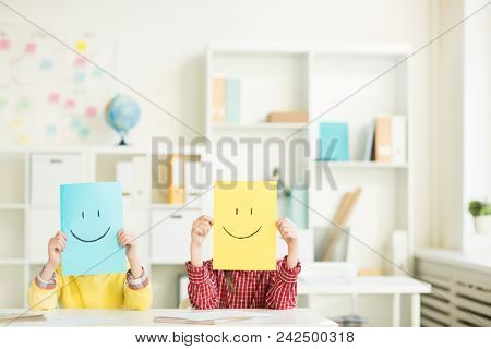 Yellow and blue papers with drawn smiles held by two youngsters by their faces