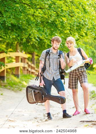 Man And Woman Tourists Backpackers Reading Map On Trip. Young Couple Hikers Searching Looking For Di