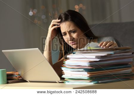 Worried Self Employed Working In The Night Looking At A Lot Of Documents