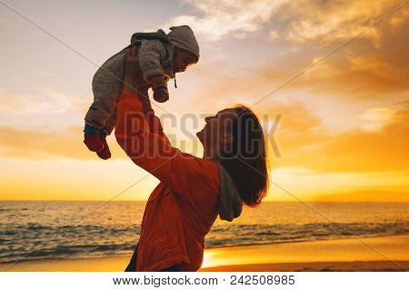 Mother And Baby Silhouettes At Sunset On The Beach Ocean In Summer. Woman And Her Child Playing Toge