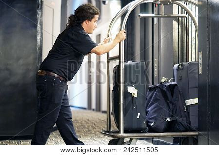 Closeup Many Suitcases On Hotel Luggage Cart Moving By Bell Boy. Baggage Porter Or Bell Boy Bringing