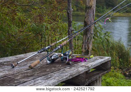 Fishing Tackle Set. Spinning Rod With Reel On Wooden Platform At Lake