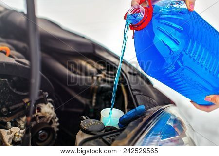 Woman Pouring Antifreeze Car Screen Wash Liquid Into Dirty Car From Blue Anti Freeze Water Container