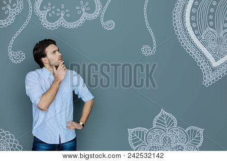 Frowning And Thinking. Calm Young Designer Frowning And Looking Attentively At The Old Drawings On T