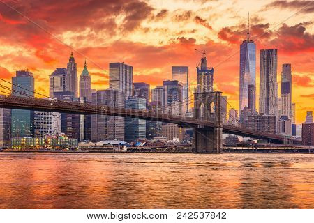 New York, New York, USA skyline of Manhattan on the East River with Brooklyn Bridge after sunset.