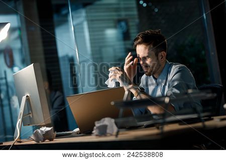 Young Man Crumpling Papers While Thinking On New Ideas Sitting At Desk In Office.