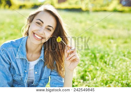 Portrait Of Attractive Woman In Jeans Sitting In A Park On The Grass At Sunny Summer Day. Joyful Smi