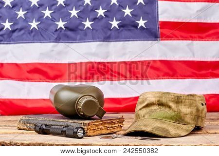 Military necessities in american flag background. Soldiers cap, bottle, book and torch. poster