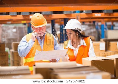 Male And Female Industrial Engineers Working At Warehouse. They Work In Industry Manufacturing Facto