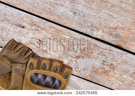 Pair Of Military Fingerless Gloves For Hiking. Wooden Desk Background. Top View, Flat Lay.