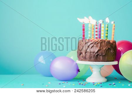 Chocolate birthday cake with colorful candles and balloons