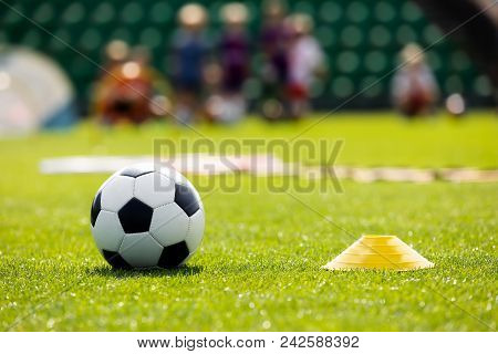 Soccer Training Equipment On A Sports Field. Football Ball And Pylon Disc Cones On A Grass Pitch. Yo
