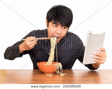 Man Eating Chinese Noodle Monstrously Whilst Looking And Using Tablet Isolate On White Background Wi