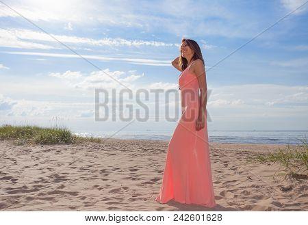 Beautiful Woman In Pink Dress On Sandy Beach .
