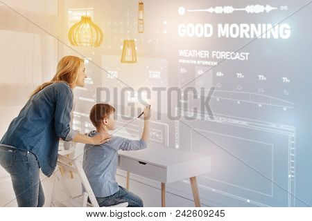 Progressive Family. Young Mother Smiling While Her Clever Progressive Child Holding A Modern Stylus