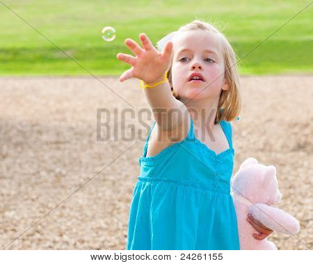 Young girl trying to catch bubble while playing at park in image with copy space