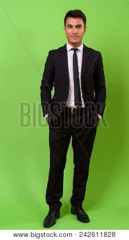 Studio Shot Of Young Handsome Hispanic Businessman Against Chroma Key With Green Background