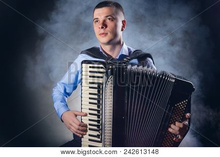Musician Playing The Accordion Against A Black Background. Fog In The Background. Studio Shot