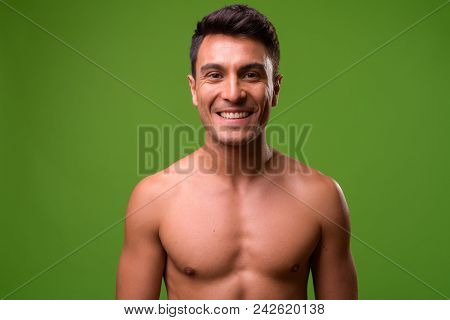 Studio Shot Of Young Handsome Hispanic Man Shirtless Against Chroma Key With Green Background