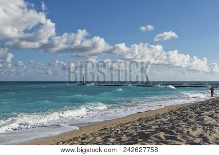 Shore Of The Atlantic Ocean, Beach, Sand With Traces Of People, Silhouette Of A Man Walking Along Th