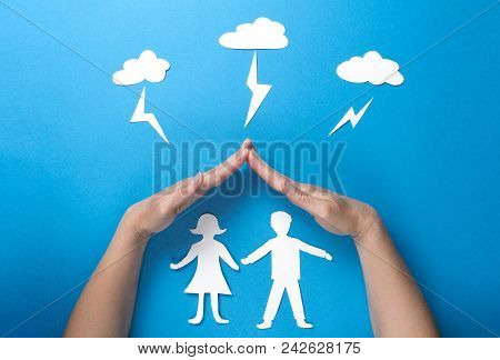 Life Insurance And Family Health Concept. Hands Protect Paper Figures Origami From Lightning From Th