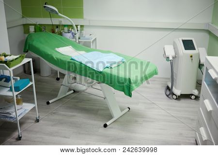 Interior of beauty parlour, green cosmetology armchair and equipment.