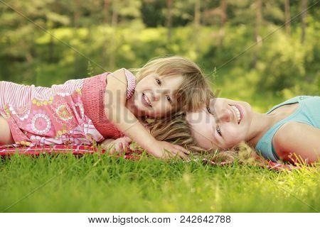 Mother With Her Cute Little Daughter Lie On The Grass