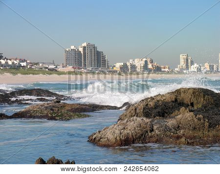 From Blouberg Strand, Cape Town, South Africa, With White Waves Washing Over Some Rocks In The Fore