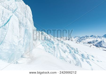 A Large Snow-covered Glacier High In The Mountains Against The Background Of The Caucasus Mountains