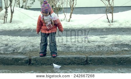 Girl In Rubber Boots Jumping On Puddle Near Wite Paper Boat 4k