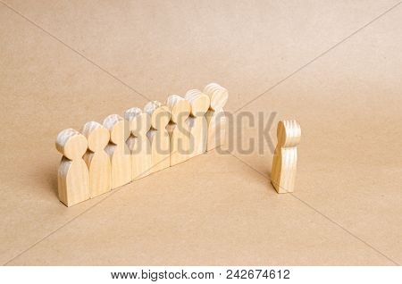 People Listen To The Leader. People Stand In Line At The Briefing And Wait For Orders. Wooden Figure