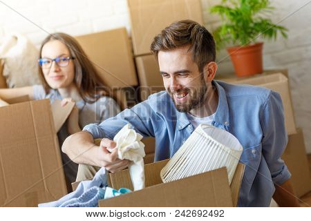 Cheerful Man And Girl Unpacking Stuff From Carton Boxes In New Apartment Having Fun.