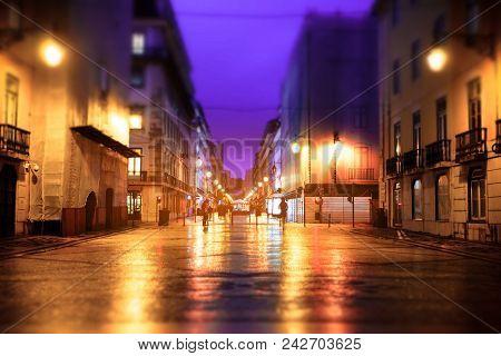 Illuminated Street Of Old European Town At Night. Tilt-shift Effect