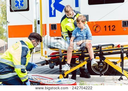Emergency doctors caring for accident victim boy sitting on stretcher