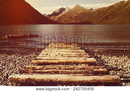 Old Wooden Pier On The Lake. Long Exposure. Landscape View With Wood Bridge In Lake And Mountain Bac