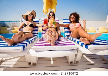 Cheers! Low Angle Shot Of Three Chics Sun Bathing Near The Pool On Striped Beach Chairs. Attractive
