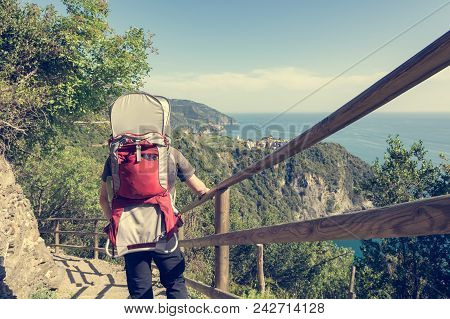 Father Carrying His Child In A Carrier Hiking A Coastal Trail. Active Fatherhood - Exploring The Wor
